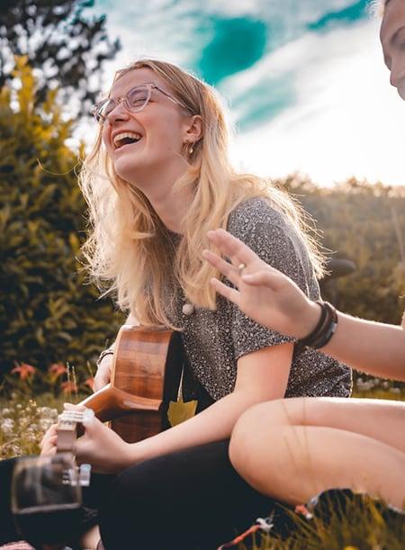 Une jeune femme rit assise dans l'herbe en jouant de la guitare.