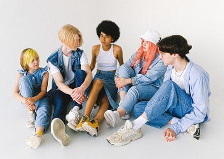 Cinq adolescents sont assis les uns à coté des autres.