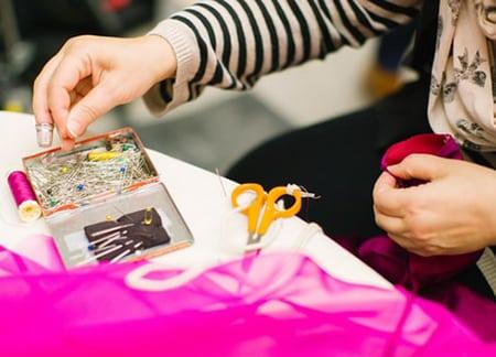 Gros plan sur des mains. L'une est entrain de prendre une aiguille dans une boite, et l'autre tient un tissu de couleur rose. Une paire de ciseaux est posée sur une table entre elle et la boite.