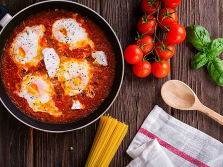 Dans une poêle il y a une sauce tomate avec des œufs. A coté de la poêle sont disposés des spaghettis non cuits, des tomates cerises et une cuillère en bois.