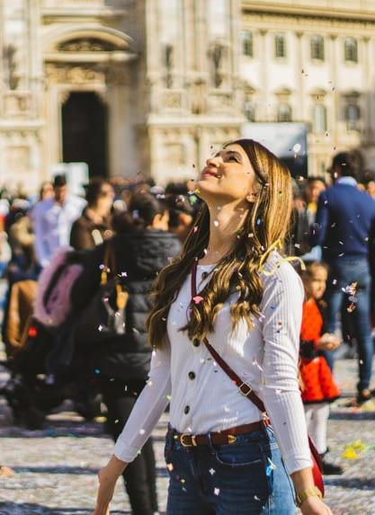 Une jeune femme, est au milieu d'une ville ou il y a du monde. Elle lève la tête en arrière avec les bras écartés. Des confettis virevoltent autour d'elle.