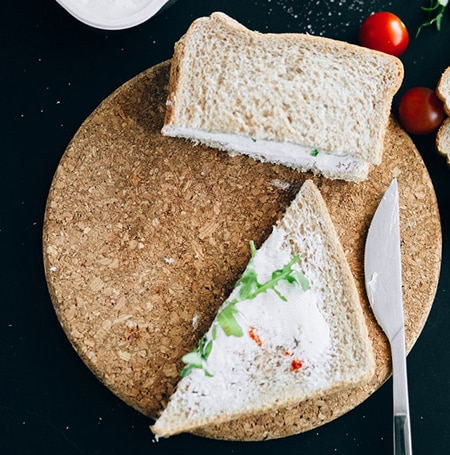 Un sandwich de pain de mie au fromage frais est posé sur une planche à découper. Il y a des tomates cerises autour.