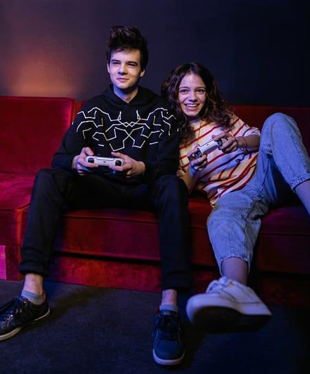 Vue de face de deux adolescents assis cote à cote dans un canapé rouge. Ils ont des manettes de console dans leurs mains et sourient.