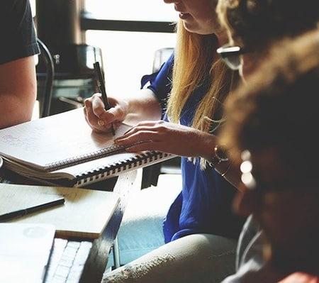 Vu de coté d'un groupe de personne en réunion. Une des participantes prend des notes.