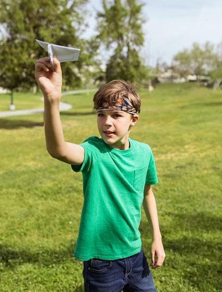 Dans un parc un enfant s'apprête à lancer un avion en papier