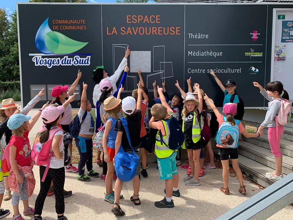 Des enfants pointent le doigt vers la pancarte d'accueil du Centre Socioculturel la Haute Savoureuse