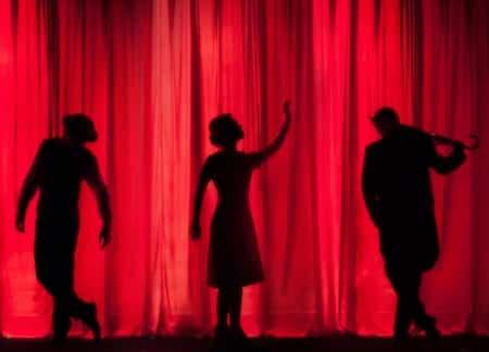 Des personnages en ombre chinoise sont derrière un rideau rouge